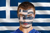 Composite image of serious young greece fan with facepaint against digitally generated greek nationa