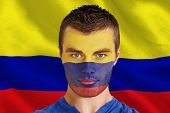 Composite image of serious young colombia fan with facepaint against digitally generated colombia na