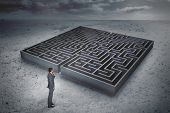 Thinking businessman against big maze under cloudy sky