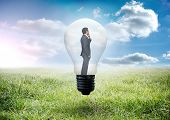 Thinking businessman in light bulb against sunny landscape