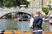 CAMBRIDGE, UK - AUGUST 18: Professional punter in Silver Street with busy River Cam full of tourists
