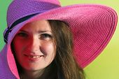 picture of pinky  - Portrait of a young woman with pinky straw hat on green background - JPG