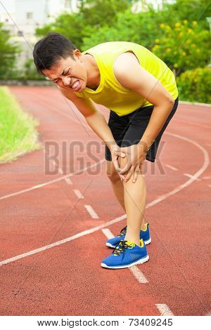 Young Male Runner Suffering From Knee Injury On The Track