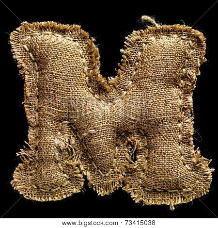 Linen or hemp vintage cloth letter M isolated on black background