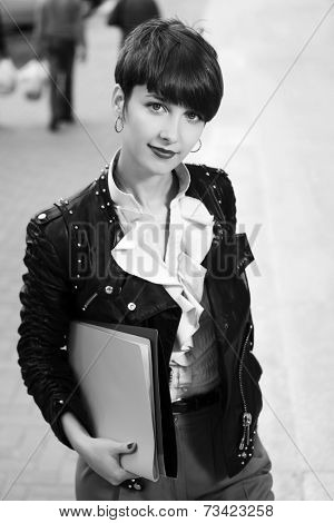 Happy young fashion business woman with a folders