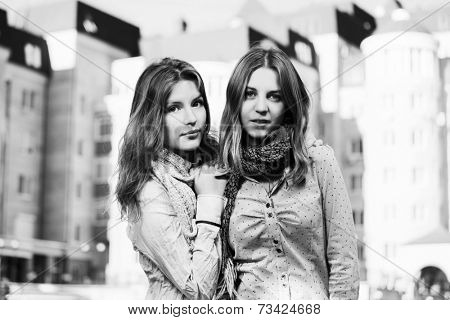 Two happy young fashion girls on the city street