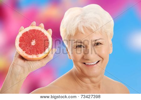 Nude old woman holding a grapefruit.