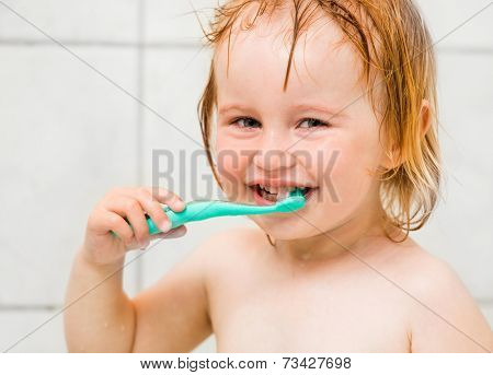 Dental hygiene. Cute baby brushing teeth in bathroom