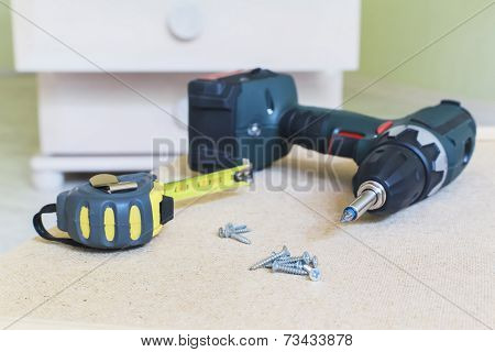 Close-up View Of Electric Screwdriver, Screws & Tape Ruler