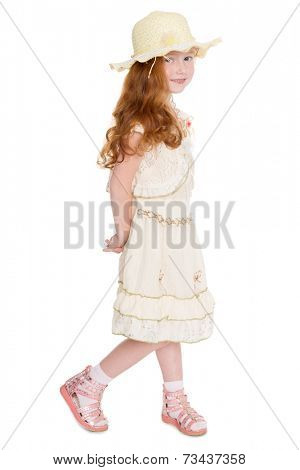 Little redhead fashionista in a summer dress and hat. Girl is six years.