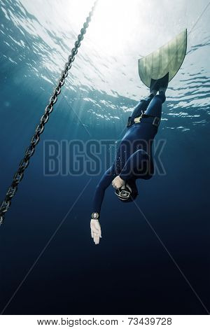 Underwater shot of free diver in monofin descending along the metal chain
