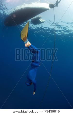 Free diver in monofin descending along the metal chain linked to the boat on surface (constant weight discipline)