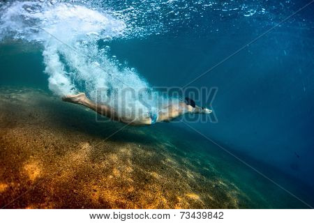 Young man gliding underwater after jump from the beach with lots of bubbles