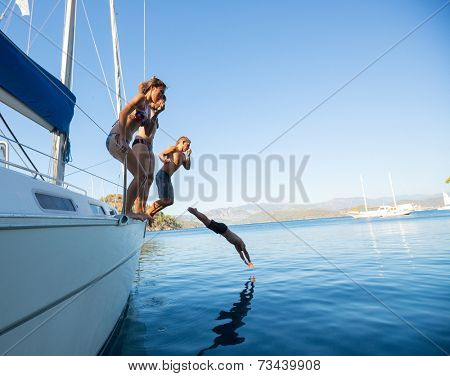 Group of young friends jumping into sea from the sail boat