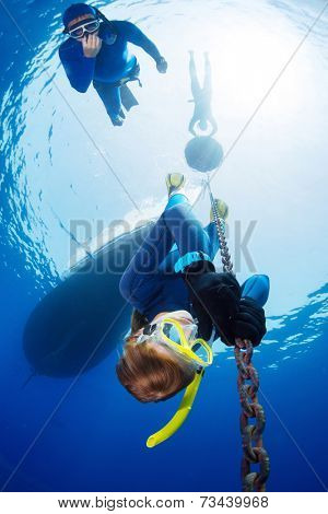 Lady free diver descending along the metal chain using his hands (free immersion). Safety buddy descending close to athlete