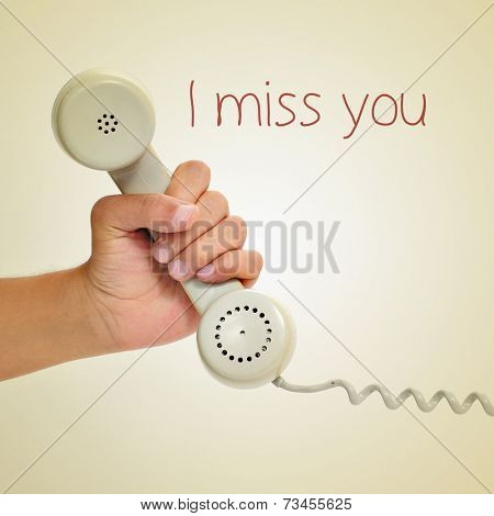 a man hand holding the handset of a telephone and the text I miss you, with a retro effect