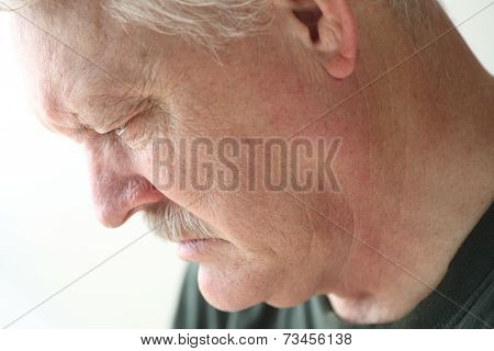 Depressed older man looking down