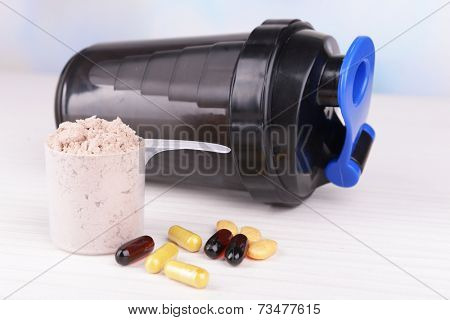 Whey protein powder in scoop with vitamins and plastic shaker on wooden background