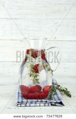Tasty cool beverage with raspberries and thyme, on light background