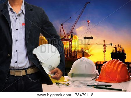 Engineer Man Wit;h White Safety Helmet Standing Against Working Table And Building Construction Scen