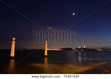 view of the wharf columns in square of commerce at moonrise, with tagus river and bridge