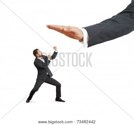 concept photo of conflict between subordinate and boss. angry young businessman showing fist and looking up at big palm of his boss. isolated on white background