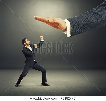 concept photo of conflict between subordinate and boss. angry young businessman showing fist and looking up at big palm of his boss. photo in the dark studio
