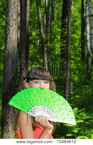 Girl covers her face with green fan