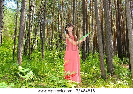 Girl in red dress in forest green fanning herself a fan