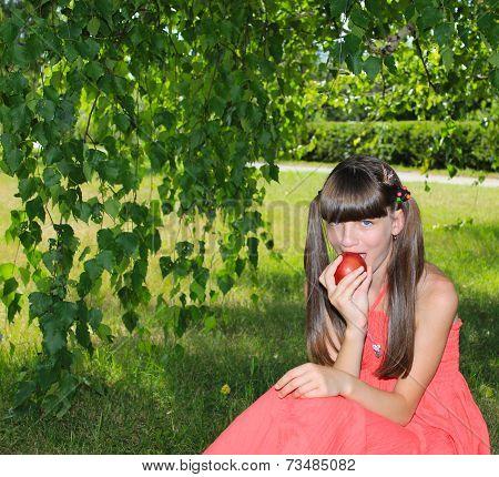 The girl bites an apple