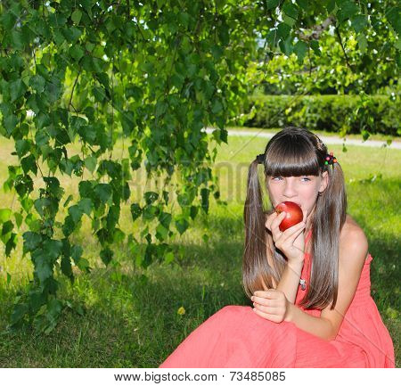 Girl eating an apple outdoors