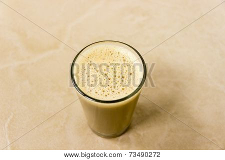 A closeup of a glass filled with freshly brewed Indian style Coffee with lather on the top
