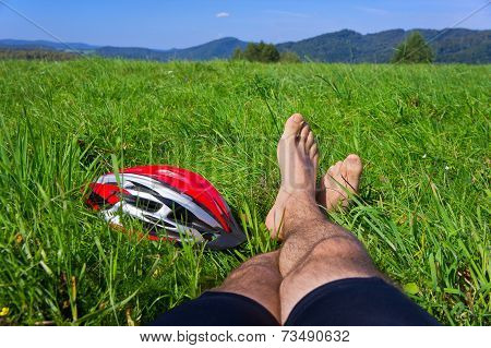 Cyclist Relax On Grass In Mountains.