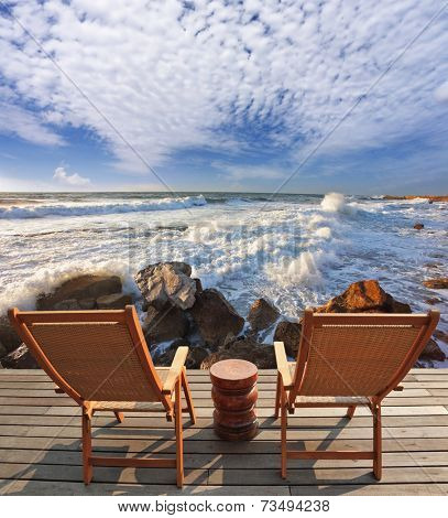 Charming lookout for two. Two convenient comfortable guest sun loungers and a bedside table are worth on a wooden platform. It is well-admired stormy sea surf
