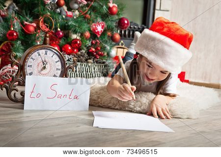 Pretty Little Girl In Santa Hat Writes Letter To Santa