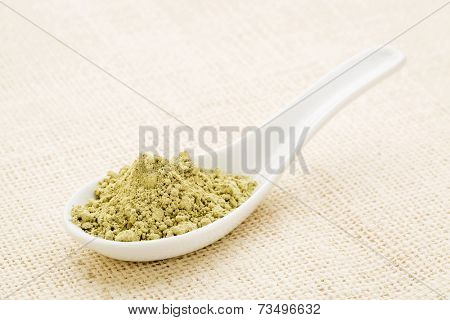 kelp seaweed powder on a white Chinese spoon against burlap canvas