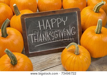 Happy Thanksgiving  - white chalk handwriting on a vintage slate  blackboard surrounded by pumpkins
