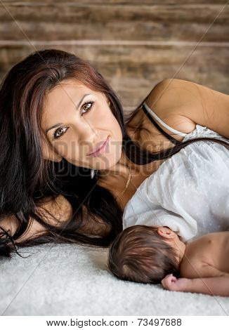 Beautiful Mother With A Newborn Lying