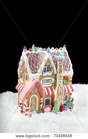 A gingerbread house in snow isolated on a black background can be used as a design element or simply for placement of copy.