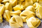image of carbohydrate  - Close up uncooked tortellini on wooden table - JPG