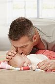 picture of fondling  - Father kissing sleeping baby tenderly - JPG