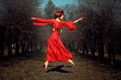 foto of float-plane  - In autumn park floating girl in a red dress with a wreath on his head like a fairy tale - JPG