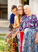 image of kindness  - Caring grandchildren supporting their kind grandmother with disabilities - JPG