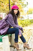 pic of knitted cap  - Young stylish woman dressed in oversized knitted sweater skinny jeans peaked cap and heels with big bag sitting on bench in city park - JPG