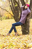 picture of knitted cap  - Young stylish smiling woman dressed in oversized knitted sweater skinny jeans peaked cap and heels having rest in city park - JPG