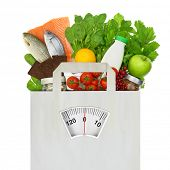stock photo of scale  - Paper bag full of groceries with weighing scale - JPG