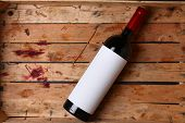 picture of crate  - Bottle of red wine with a blank label in a used wooden crate with grape juice marks - JPG