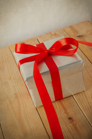 pic of box-end  - Tilted shot of a silver gift box tied to a bow in satin red ribbon - JPG