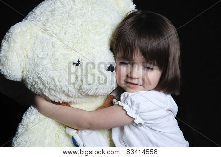 a little girl with bear on a black background