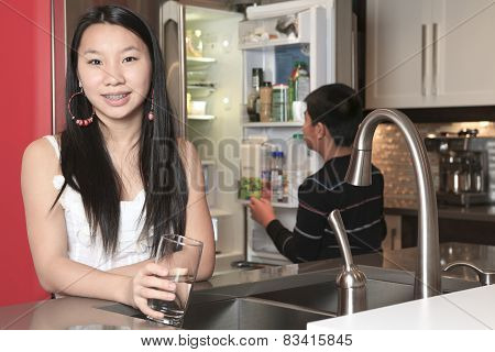 A teenager girl drinking water in the kitchen